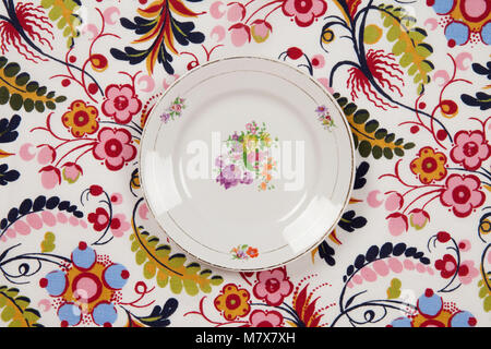 a flower plate hidden on a flowery fabric. Camouflage game. Minimal color still life photography. - Stock Photo