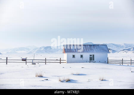 small white house in a snow covered valley in the middle of mountains of Northern Mongolia - Stock Photo