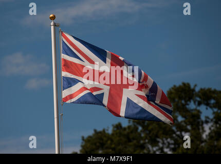 Union Jack Flag blowing in the wind against a sunny blue sky - Stock Photo