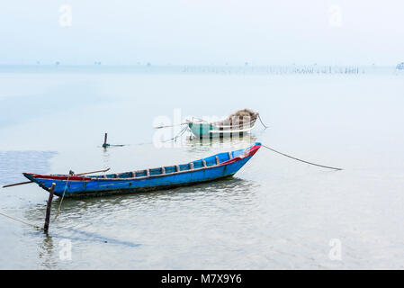 Bamboo and wood traditional fishing boats tied up on the beach at Lap An Lagoon, Vietnam, with a large oyster farm - Stock Photo