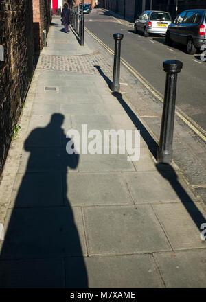 shadow of figure on street in bright sunlight - Stock Photo