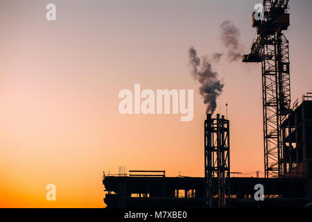 Crane and building construction site with pipe with smoke on background of sunset sky. Industrial landscape with - Stock Photo