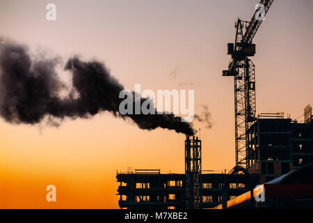 Atmospheric air pollution from industrial smoke. Crane and building construction site with pipe with smoke on background - Stock Photo