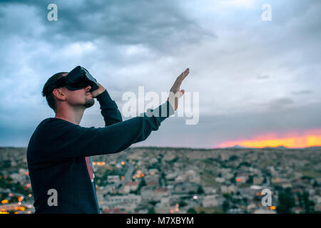 A man in virtual reality glasses on the background of a sunset over the city. Concept of modern technologies. - Stock Photo