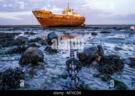 Rusty old fishing vessel marooned at low tide on a mud bank the boats long big anchor chain goes from the centre - Stock Photo