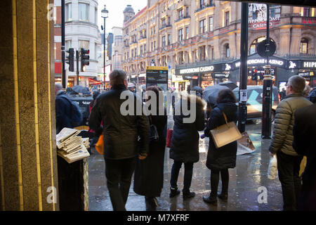Leicester Square Station Exit with People Sheltering from Rain on Charing Cross Rd, London UK - Stock Photo
