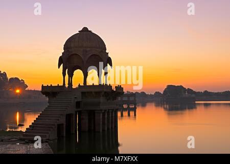 Sunrise over Gadi Sagar Temple in Gadisar lake, Jaisalmer, Rajasthan India - Stock Photo