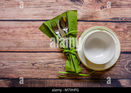 Silverware tied with ribbon on a green napkin and china on wooden table, top view - Stock Photo