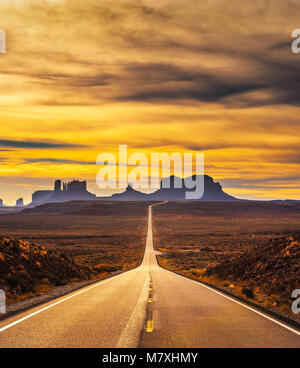Desert road leading to Monument Valley at sunset - Stock Photo