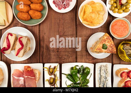 The food of Spain. An overhead photo of many different Spanish tapas, shot from above on a dark rustic texture. - Stock Photo