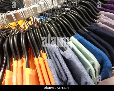 Rainbow colored clothes on hangers in a retail shop. Fashion and shopping concept - Stock Photo