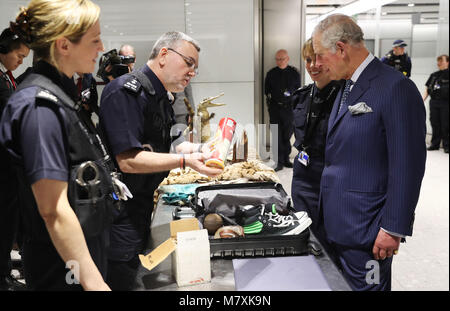 The Prince of Wales (right) is shown items of luggage that have been confiscated during inspections by customs officers - Stock Photo