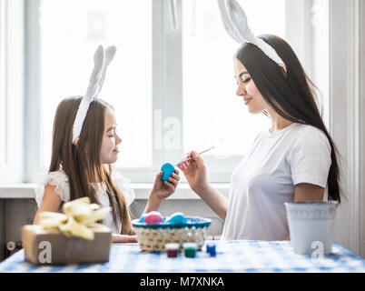 little girl painting easter eggs with mother - Stock Photo