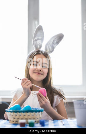 a happy little girl painting easter eggs - Stock Photo