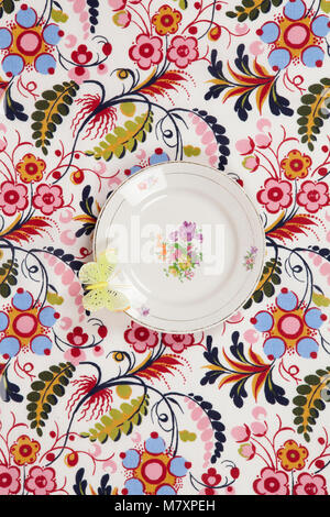 a flower plate hidden on a flowery fabric with a yellow butterfly on the edge. Camouflage game. Minimal color still - Stock Photo