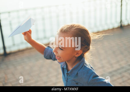 Close-up  of girl playing, running with toy paper airplane in the park, on gray pavage near lake in denim dress. - Stock Photo