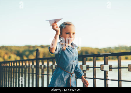 Close-up portrait of child playing, running with toy paper airplane in the park, near lake in denim dress looking - Stock Photo