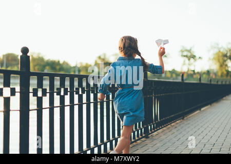 Back view of child playing, running with toy paper airplane in the park, on gray pavage near lake in denim dress. - Stock Photo