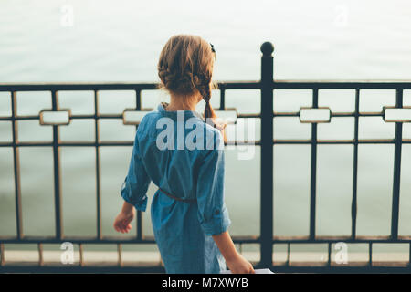 Close-up back view of child playing in the park looking yo lake in denim dress. Girl looking in the future. - Stock Photo