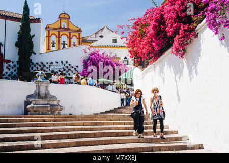 Cordoba, Andalusia, Spain : Two women walk past bougainvillea flowers in the stairway of the Cuesta del Bailio street - Stock Photo