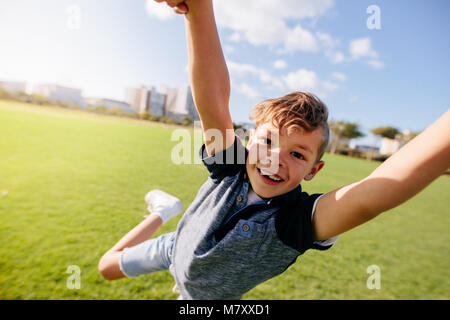 Close up of a boy jumping in air at a park. Cheerful boy enjoys being lifted in air while playing in a park. - Stock Photo
