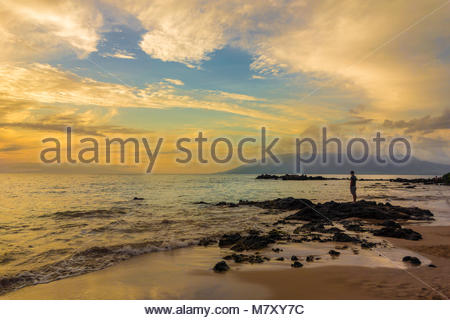 Tropical sunset at Kamaole Beach Park 3 on the beach and Pacific Ocean on the island of Maui in the state of Hawaii - Stock Photo