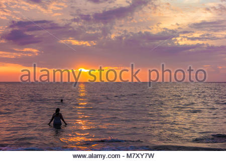 Bathers and tropical sunset at Kamaole Beach Park 3 on beach and Pacific Ocean on the island of Maui in the state - Stock Photo