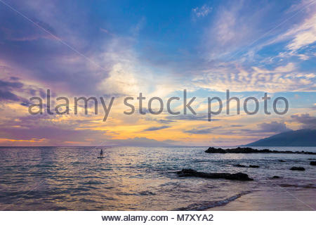 Paddleboarding and tropical sunset at Kamaole Beach Park 3 Pacific Ocean on the island of Maui in the state of Hawaii - Stock Photo