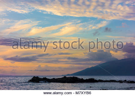 Tropical sunset from Kamaole Beach Park 3 over the Pacific Ocean on the island of Maui in the state of Hawaii USA - Stock Photo