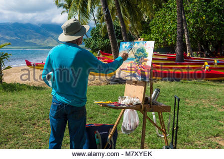 Artist painting en plein air outdoors outrigger canoes in Kihei on the island of Maui in the State of Hawaii USA - Stock Photo