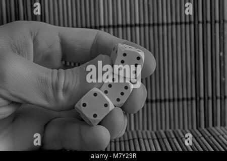 Monochrome Stack of three white plastic dices in man's hand on brown wooden table background. Six sides cube with - Stock Photo