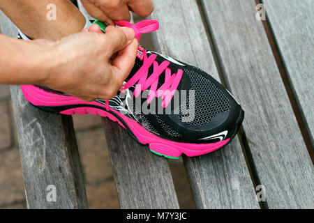 A woman fastening her running shoes - Stock Photo
