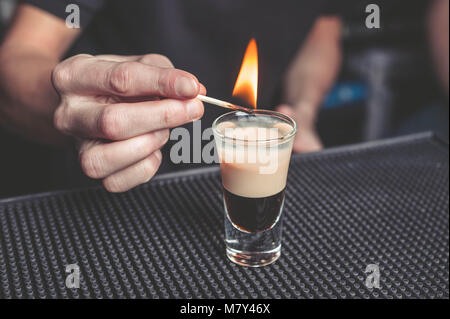 Barman flaming cocktail B-52 on the bar - Stock Photo