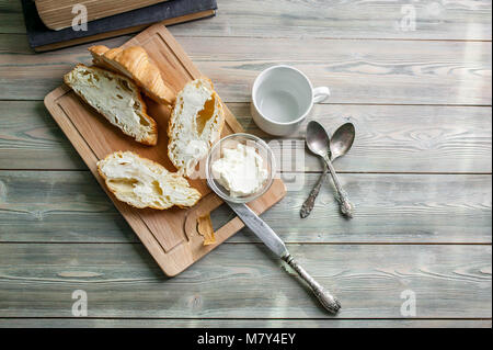 Fresh baked croissants with butter on a chopping board on a wooden table. Breakfast concept. Top view - Stock Photo