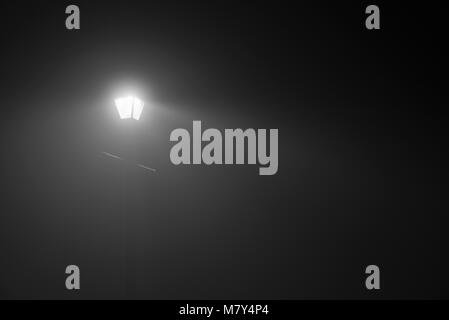 Upper portion of streetlamp on a foggy night in monochrome - Stock Photo