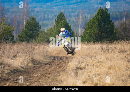 Pribram, Czech republic - 11.03.2018: Motocross rider in action on the off-road in nature next to small czech town - Stock Photo