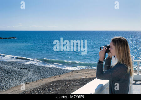 Young millennial female of Caucasian ethnicity holding a camera and taking a photograph facing towards the ocean, - Stock Photo