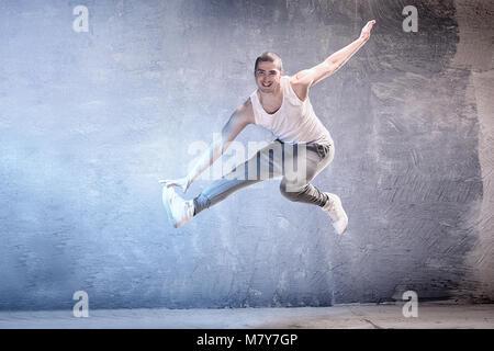 Modern male dancer jumping, smiling. - Stock Photo