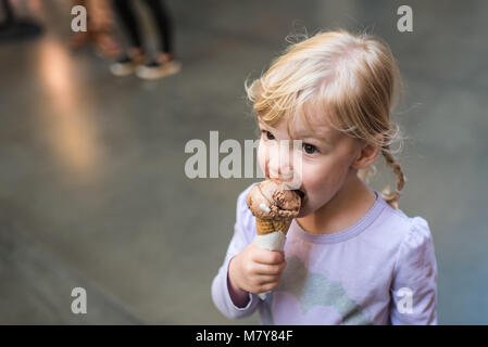 child eating ice cream cone in marketplace - Stock Photo