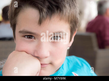 child with brown wide open eyes,brown hair and the hand in his face  looking us - Stock Photo