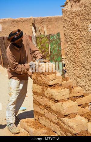 Saharawi man builds a mud bricks house in Smara, Sahawi refugees camp in Algeria. - Stock Photo