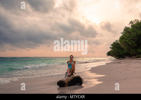 Beautiful girl sitting on a piece of wood on a solitary beach at sunset, front view - Stock Photo