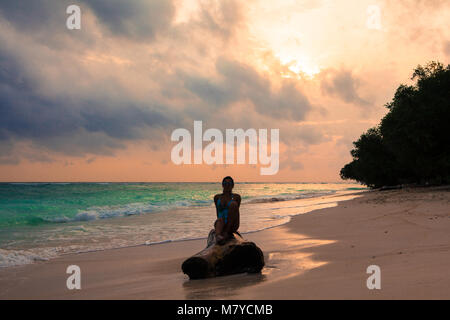 Silhouette of girl sitting on a piece of wood on a solitary beach at sunset, front view - Stock Photo