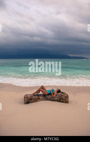 Beautiful girl laying on a tree trunk in the sand of a solitary beach at sunset, with turquoise blue water and dramatic - Stock Photo