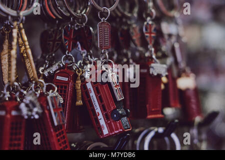 London red post box and red bus souvenir key chains on sale at a street market. - Stock Photo