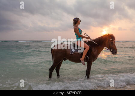 Beautiful girl riding a horse in the water, on the deserted beach of Gili Trawangan island, Indonesia, looking at - Stock Photo