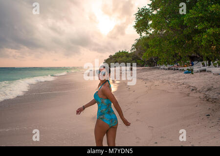 Beautiful girl with one piece swimsuit and sunglasses, running and smiling looking at the camera on the beach at - Stock Photo
