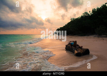 Girl laying on a piece of wood on a deserted beach with pink sunset, diagonal perspective view - Stock Photo
