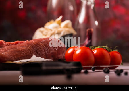 Horizontal photo of few red cherry tomatoes. The vegetable is placed on vintage wooden board next to raw pork tenderloin - Stock Photo