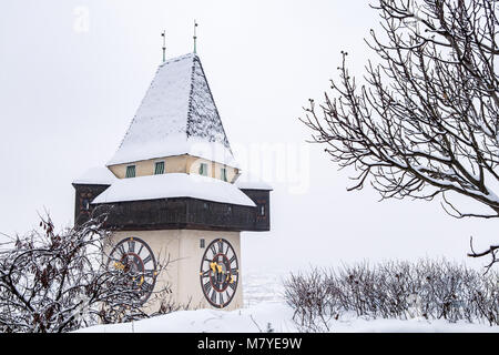 Snow covered Uhrturm clocktower landmark of city Graz on hill Schlossberg in winter - Stock Photo